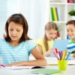Girl drawing with schoolmates — Stock Photo