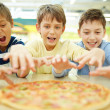 Boys eating pizza — Stock Photo