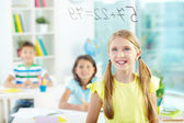Girl looking at sums on transparent board — Stock Photo