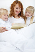 Mother reading to her daughters — Stock Photo