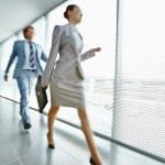 Businesswoman walking along corridor — Stock Photo