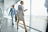 Businesswoman walking along corridor — Stock Photo
