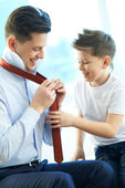 Boy looking at his father tying necktie — Stock Photo