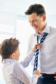 Boy helping his father tie necktie — Stock Photo