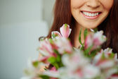 Toothy smile and flowers — Stock Photo