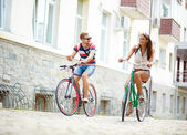 Girl and guy cycling — Stock Photo