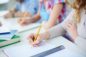 Groupmates writing lecture — Stock Photo