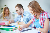 Girl and her groupmates working at lesson — Stock Photo