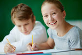 Schoolgirl drawing with her classmate — Stock Photo