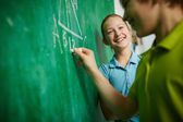Girl and her classmate by blackboard — Stock Photo
