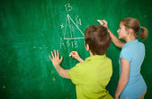 Classmates by the blackboard — Stock Photo
