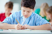 Schoolboy drawing at workplace — Stock Photo