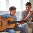 Boy playing guitar with father — Stock Photo #46332857