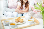 Teacups and cupcakes on tray with little girl — Stock Photo