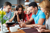 Friends using gadgets in cafe — Stock Photo