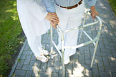 Disabled woman with walking frame — Stock Photo