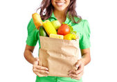 Girl with packet full of fruits and vegetables — Stock Photo