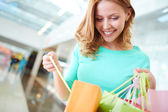Girl  looking into shopping bags — Stock Photo