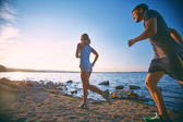 Couple running on the coastline — Stock Photo
