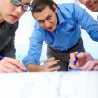 Business people bending over draft — Stock Photo #47629737