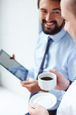 Businessman holding cup and listening tocolleague — Foto Stock