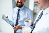 Businessman holding cup and listening tocolleague — Stock Photo