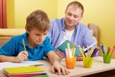 Schoolboy doing schoolwork at home — Stock Photo
