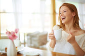 Woman with cup of coffee laughing — Stock Photo