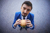 Businessman with sandwich — Stock Photo