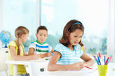 Girl drawing with her schoolmates — Stock Photo