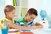 Girl and her classmate drawing — Stock Photo