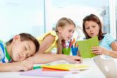Schoolgirl showing classmate notes — Stock Photo