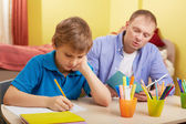Schoolboy and father making schoolwork — Stock Photo