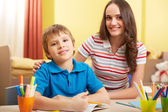 Schoolboy and mother making schoolwork — Stock Photo