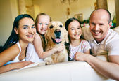 Friendly family of four with dog — Stock Photo