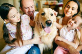 Family of four cuddling their dog — Stock Photo