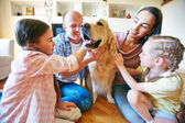 Family of four cuddling their dog — Stock Photo