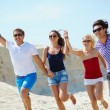 Young people running down sandy beach — Stock Photo #49267395
