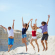 Young people jumping over sandy beach — Stock Photo #49267397