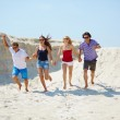 Young people running on the sand — Stock Photo #49267399