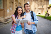 Travelers with map of ancient town — Stock Photo