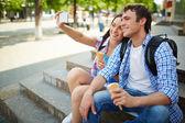 Travelers with ice-cream taking photo — Stock Photo