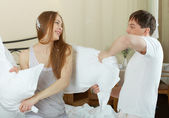 Couple playing with pillows — Stock Photo
