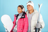 Girl and man holding snowboard and skis — Stock Photo