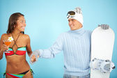 Girl in bikini and man holding snowboard — Stock Photo