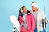 Girl and man in winterwear holding snowboard — 图库照片