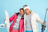 Girl and man holding snowboard and skis — 图库照片