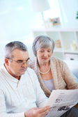 Couple of pensioners reading newspaper — Stock Photo