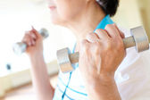 Aged woman exercising with barbells — Stock Photo