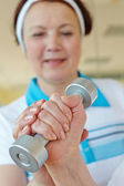 Woman doing physical exercise with barbells — Stock Photo